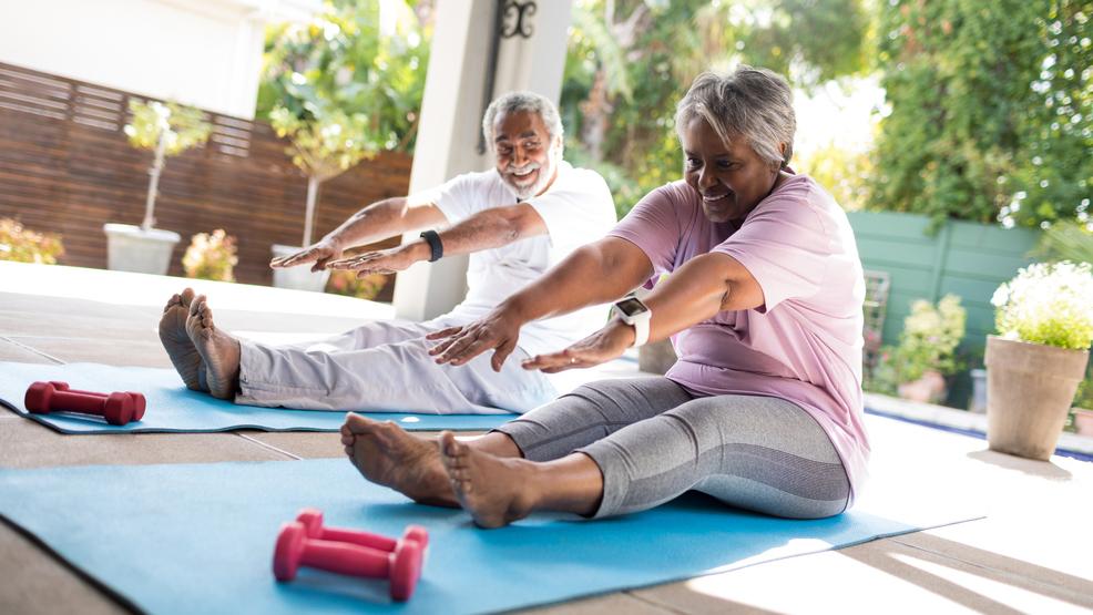 Full length of senior stretching exercise on mat in yard